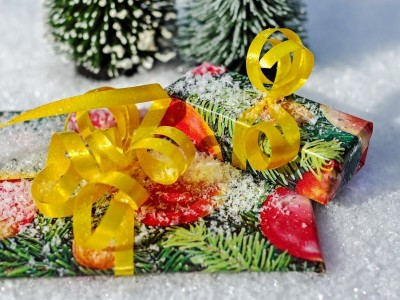 Christmas presents tied with yellow ribbon sitting in snow