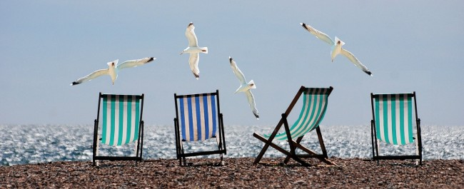 seagulls soaring over deckchairs on a pebble beach think about your digital marketing strategy for the tourism industry